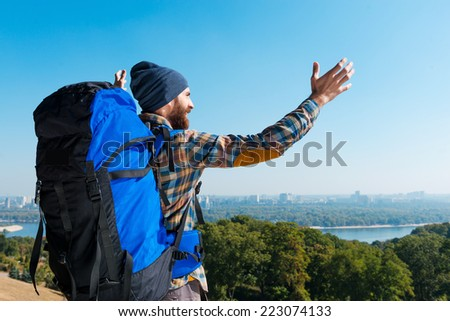 Happy of being a part of it! Handsome young man carrying backpack and looking at view with raising arms