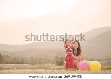 Happy of mother and son playing in outdoors at sunset - stock photo