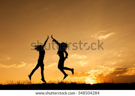 Happy of two women jumping and sunset silhouette with copy space. - stock photo