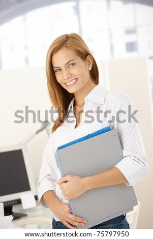 Happy office girl standing with folders handheld, smiling at camera.? - stock photo