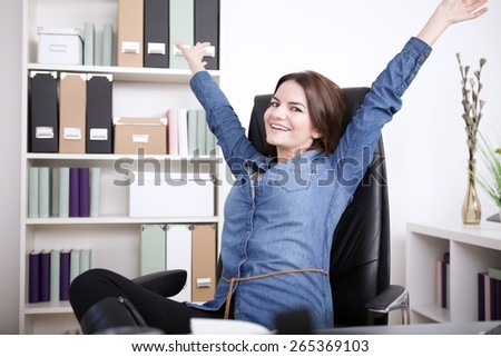 Happy Office Woman in Denim Blouse Sitting on her Office Chair While Extending her Arms and Looking at the Camera.