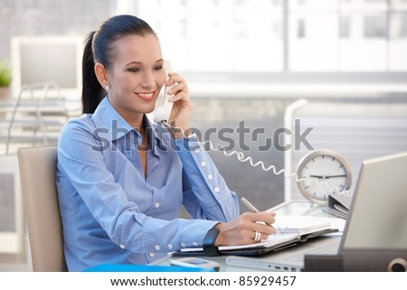 Happy office worker girl on landline phone call, smiling, listening to conversation.? - stock photo