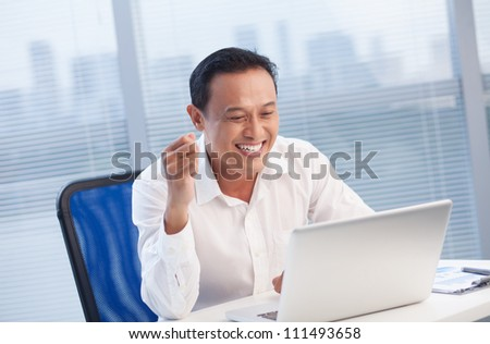 Happy office worker looking with excitement at laptop at office - stock photo