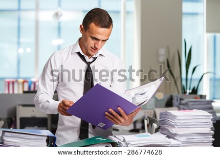 Happy office worker works with folders of paper