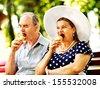 Happy old couple eating ice-cream outdoor. - stock photo