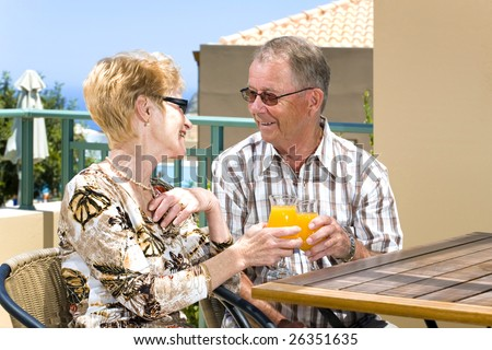 happy old couple enjoying their lunch on the balcony - stock photo