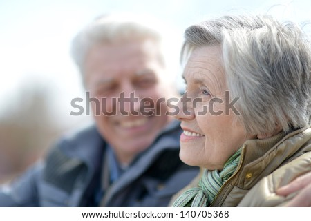 happy old couple on a walk in the park in spring - stock photo