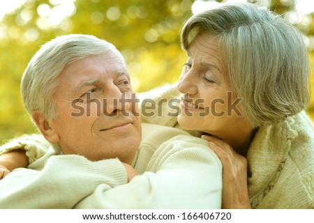 Happy old couple posing at autumn park - stock photo