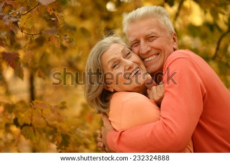 Happy old couple posing at autumn park
