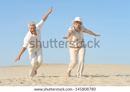 happy old couple walking barefoot on the sand in the summer - stock photo