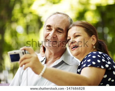Happy old couple with camera take pictures. - stock photo
