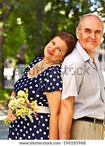 Happy old couple with flower back to backoutdoor. - stock photo