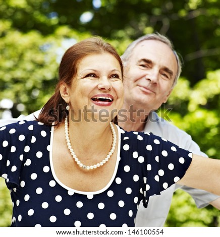 Happy old couple with flower outdoor. - stock photo