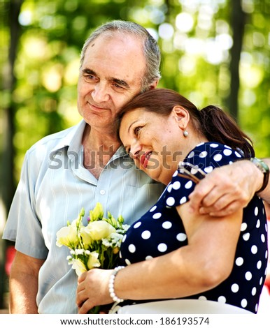 Happy old couple with flower outdoor.