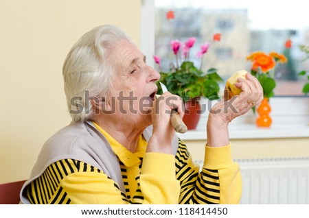 Happy old gray-haired woman eating apple