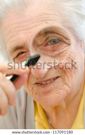Happy old gray-haired woman with magnifier - stock photo