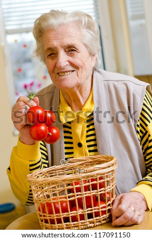 Happy old gray-haired woman with tomato