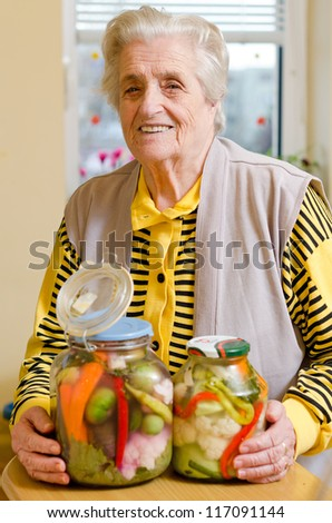Happy old gray-haired woman with veggies - stock photo