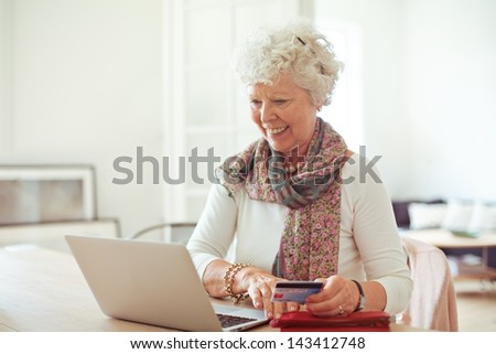 Happy old lady doing some shopping online using her laptop - stock photo