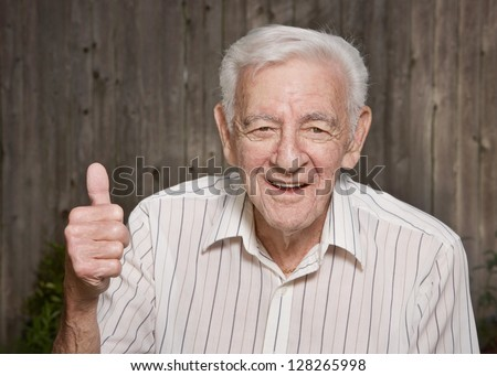 Happy old man giving thumbs up - stock photo