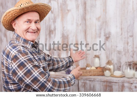 Happy old man is showing dairy products on the table and smiling. He is standing and pointing his arms sideways - stock photo