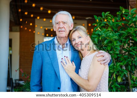 Happy old senior couple in town. Proud Elderly man hugs wife. Summer evening time with backlight - stock photo