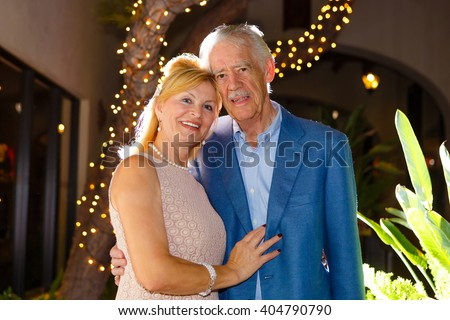 Happy old senior mature couple in town. summer evening time with backlight - stock photo
