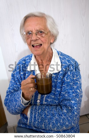 Happy old woman holding a cup of coffee while smiling.