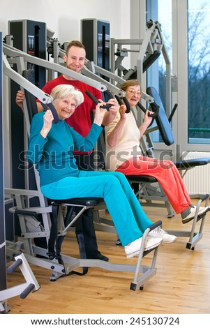 Happy Old Women Exercising Chest Press Workout at the Fitness Gym Assisted by Young Male Instructor.