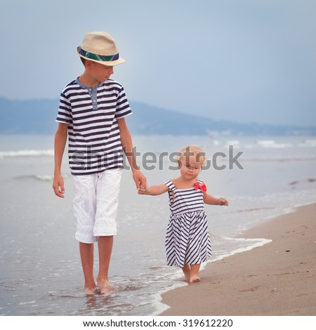 Happy older brother and younger cute sister walking on sea coast. Italy - stock photo
