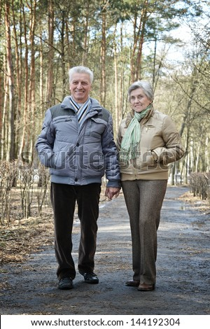 happy older couple on a walk in the forest in the spring - stock photo