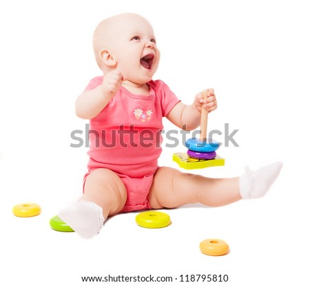 happy one year old baby playing with a pyramid, isolated against white background