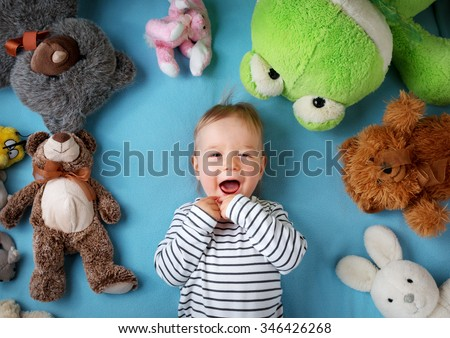 Happy one year old boy lying with many plush toys on blue blanket - stock photo