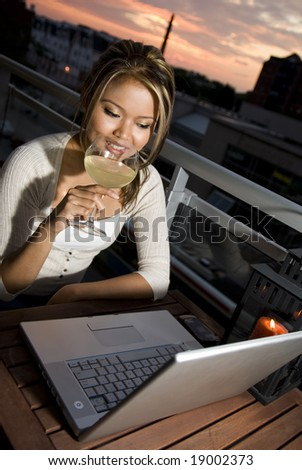 happy online chat outside with glass of wine - stock photo