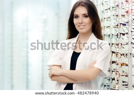 Happy Optician Standing in Optical Store - Young female optometrist in optics shop