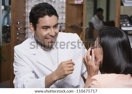 Happy optometrist assisting patient in choosing glasses