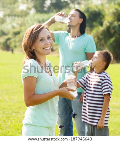 Happy ordinary  couple with teenager drinking water from plastic bottles in summer