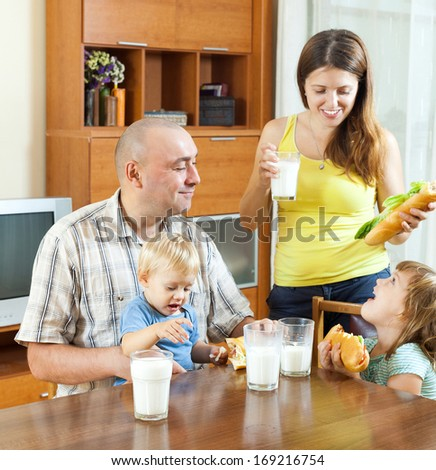 happy ordinary family of four eating sandwiches at home interior