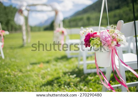 Happy outdoor Wedding Ceremony Scene for a summer mountain wedding. Wedding aisle, decorated wedding alter and flower decorations with mountains in the background. - stock photo