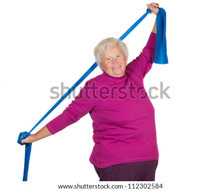 Happy overweight senior lady exercising stretching her arms above her head using a strap to improve her flexibility and strengthen her neck and shoulder muscles - stock photo
