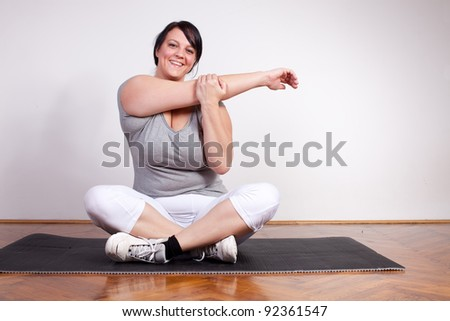 Happy overweight woman exercising/stretching - stock photo