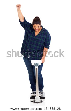 happy overweight woman waving fist on scale as she has lost weight - stock photo