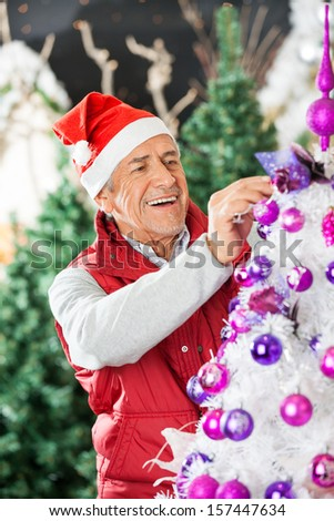 Happy owner in Santa hat decorating Christmas tree at store - stock photo
