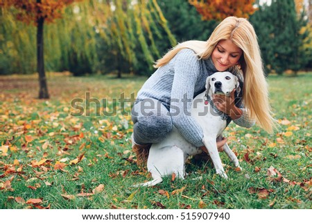 Happy owner woman kissing Dalmatian dog in autumn park