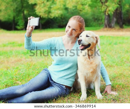 Happy owner woman with Golden Retriever dog taking selfie portrait on smartphone in summer day - stock photo