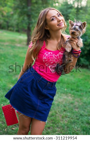 Happy owner woman with yorkshire terrier dog in sunglasses on the grass in summer day - stock photo