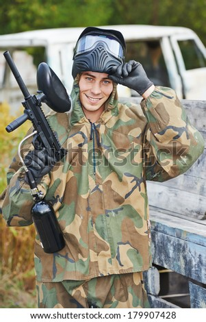 Happy paintball sport player man in protective camouflage uniform and mask with marker gun outdoors - stock photo