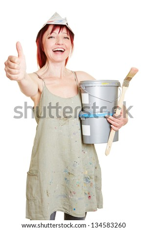 Happy painter with brush and paint buckets holding thumbs up - stock photo