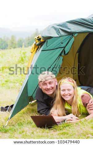 Happy pair in tent works on a laptop against mountains - stock photo