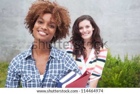 Happy pair of students holding notebooks outdoors - stock photo